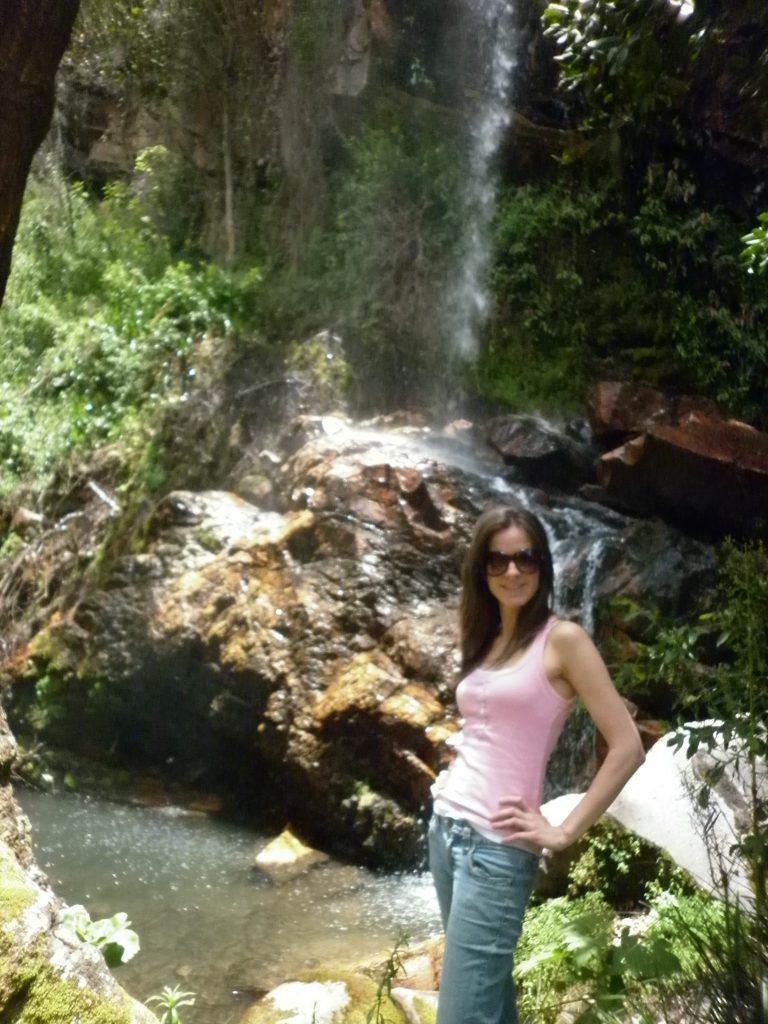 Anna striking a pose next to a waterfall on the trail to the scenic outlook